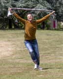 Excited 40s man expressing euphoria and freedom in park. Celebrating success outdoors concept - smiling young man running wild in a park with scarf in hands for Royalty Free Stock Image