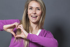Excited 20s woman showing heart shape with hands Royalty Free Stock Images