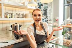 Excited saleswoman using mobile phone in cafeteria Stock Photos