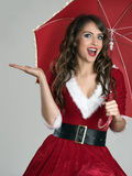 Excited Santa helper girl under umbrella with open palm Royalty Free Stock Photos