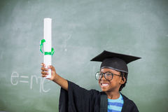 Excited schoolboy in mortar board holding certificate in classroom. At school Stock Photo