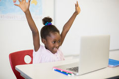 Excited schoolgirl with laptop in classroom. At school Stock Photo