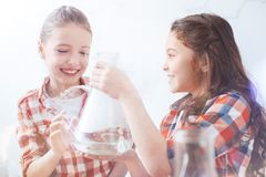 Excited schoolgirls grinning widely while holding flask in school lab. So much fun. Two young ladies getting pretty excited while holding a fuming vacuum flask Stock Photos