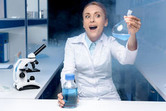 Excited scientist working with reagent in flask in laboratory. Portrait of excited scientist working with reagent in flask in laboratory Royalty Free Stock Photography