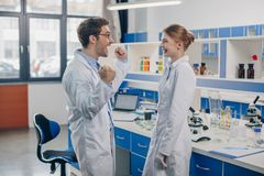 Excited scientists in laboratory. Excited scientists in white coats working in laboratory Royalty Free Stock Photo