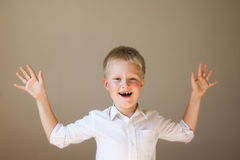 Excited screaming boy. Happy excited screaming boy (child) in white shirt, hands up, over grey background Stock Photo