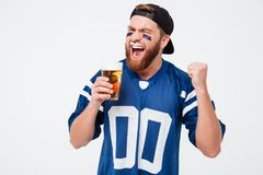 Excited screaming man fan drinking beer make winner gesture. Royalty Free Stock Photos