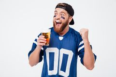 Excited screaming man fan drinking beer make winner gesture. Stock Photo