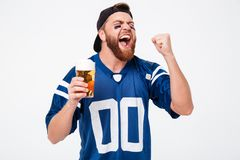 Excited screaming man fan drinking beer make winner gesture. Royalty Free Stock Image