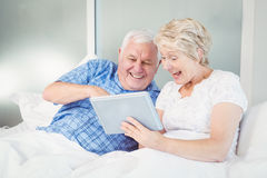 Excited senior couple using digital tablet at home Stock Image