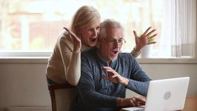 Excited senior couple winners using laptop overjoyed by online win. Excited happy senior old family couple winners using laptop overjoyed by unbelievable online