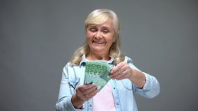 Excited senior female counting euro banknotes, planning purchases, loan service. Stock photo royalty free stock photo
