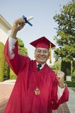 Excited Senior Graduate Holding Degree Royalty Free Stock Photo