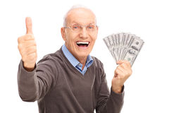Excited senior holding money and giving a thumb up. Excited senior gentleman holding a stack of money and giving a thumb up isolated on white background Stock Photo