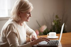 Excited senior lady browsing web using laptop at home. Excited aged woman using laptop, browsing internet at home, smart senior lady working at computer drinking stock photography