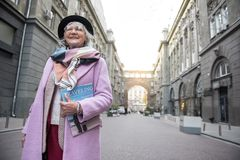 Excited senior lady standing with journal on street. Low angle of happy stylish mature woman traveling in city with enjoyment. She is carrying magazine and royalty free stock photography