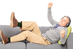 Excited senior male seated on a modern couch listening music Royalty Free Stock Photos