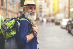 Excited senior male traveler enjoying walk in town. I like traveling. Portrait of happy old man walking in city and smiling. He is carrying rucksack. Copy space Stock Photo