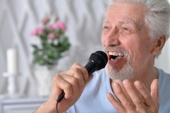 Excited senior man holding microphone. Portrait of excited senior man holding microphone Royalty Free Stock Images