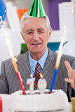 Excited senior man looking at his birthday cake. For 70th birthday Royalty Free Stock Images