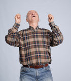 Excited senior man with raised hands Stock Images