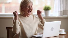 Excited senior woman feeling winner reading good online news
