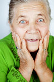 Excited senior woman with surprise expression. On her face Stock Images