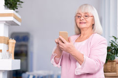 Excited senior woman using her phone Stock Photography