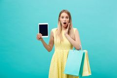 Excited shocked good-looking young woman in yellow dress while holding tablet and shopping bags. Excited shocked good-looking young woman in yellow dress while Royalty Free Stock Photo