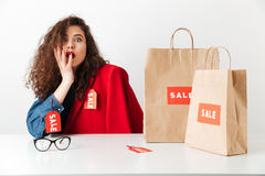 Excited shocked sale woman sitting with paper shopping bags. Isolated over white background Stock Images