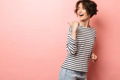 Excited shocked surprised beautiful woman posing isolated over pink wall background pointing stock photos