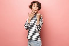 Excited shocked surprised beautiful woman posing isolated over pink wall background pointing royalty free stock images