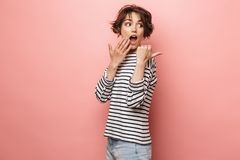 Excited shocked surprised beautiful woman posing isolated over pink wall background pointing stock photo