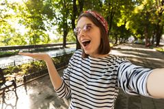 Excited shocked woman outdoors take a selfie by camera showing copyspace. stock images