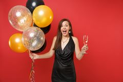 Excited shocked young woman in black dress celebrating, holding glass of champagne, air balloons isolated on red royalty free stock images
