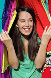 Excited shopper. Young happy woman peeping through clothes rail Stock Images