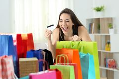 Excited shopper looking at multiple purchases. In colorful shopping bags at home Stock Photos
