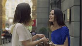 Excited shopper woman showing purchase to her friend stock footage