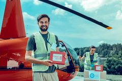Excited short-haired guy working as volunteer and holding first aid box stock photo
