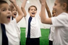 Excited shout. Ecstatic participants of football games in uniform raising their hands and shouting Stock Photography