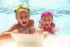 Excited siblings using laptop and shouting in pool. Portrait of excited little siblings wearing goggles sitting in swimming pool with laptop, looking at camera Royalty Free Stock Images