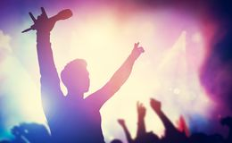 Excited singer raising hands on stage stock photo