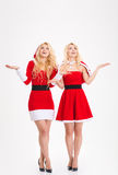 Excited sisters twins in santa claus costumes waiting for snow Stock Photos