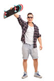Excited skater holding his skateboard in the air. Full length portrait of an excited male skater holding his skateboard in the air and looking at the camera Stock Image