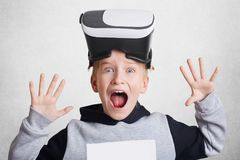 Excited small boy touches air during VR experience. Little child wears virtual reality headset on head, explores something, gestur Royalty Free Stock Image