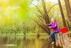 Excited small girl fishing near beautiful pond Royalty Free Stock Photos
