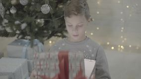 Excited small happy child boy opening christmas present gift box in decorated new year tree festive atmosphere room stock video footage