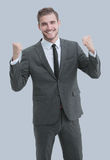 Excited smile business man raised arms, isolated over gray backg. Portrait of successful business man winner celebrating Stock Image