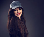 Excited smiling beautiful brunette woman in baseball blue cap wi Stock Image