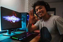 Excited smiling gamer boy rejoicing victory while playing video. Games on computer in dark room wearing headphones and using backlit colorful keyboard royalty free stock images